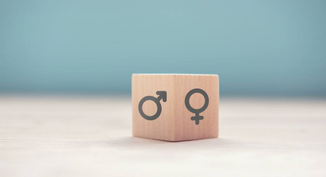 A wooden block with symbols for gender on each side against a white and blue background.