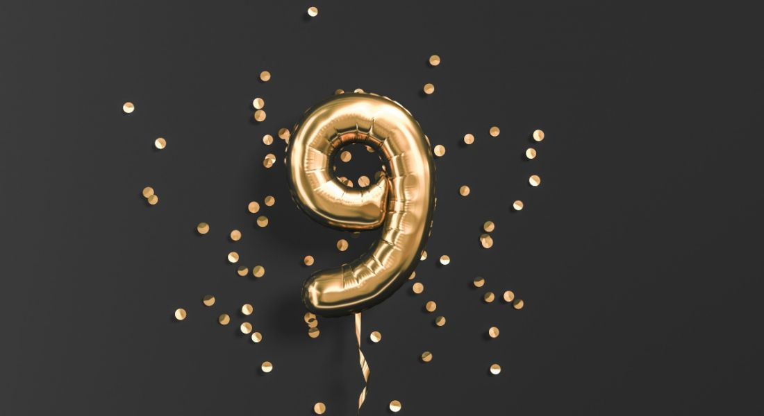 Number nine gold foil balloon and gold confetti on black background.