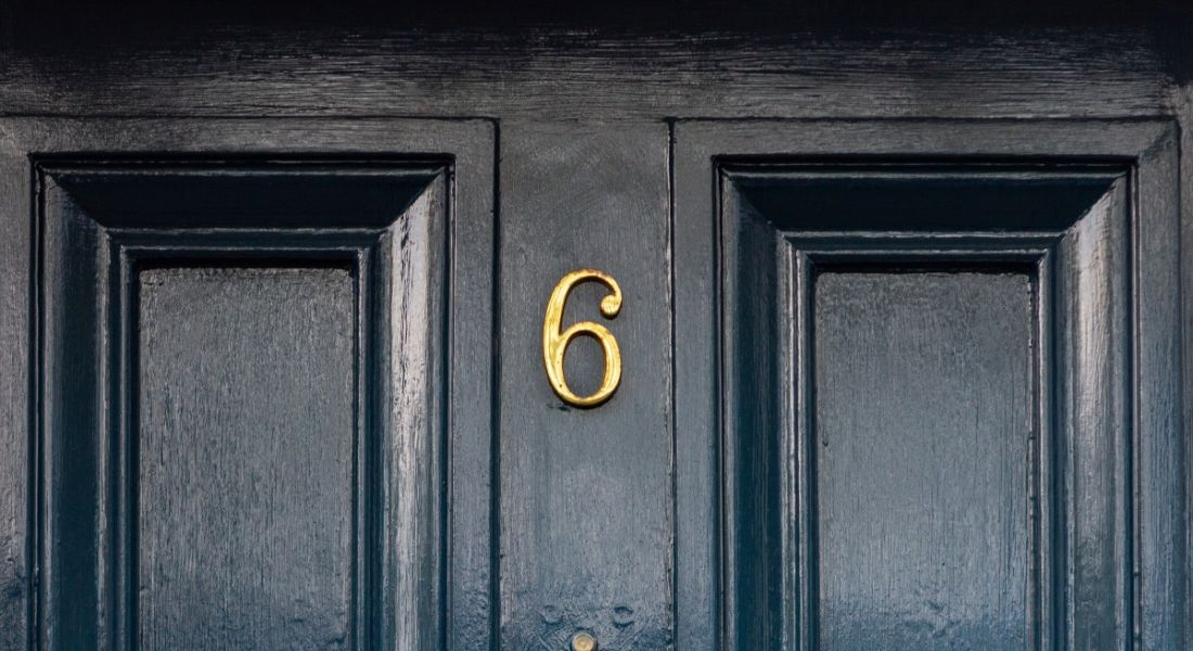 Number six on a dark blue front door.