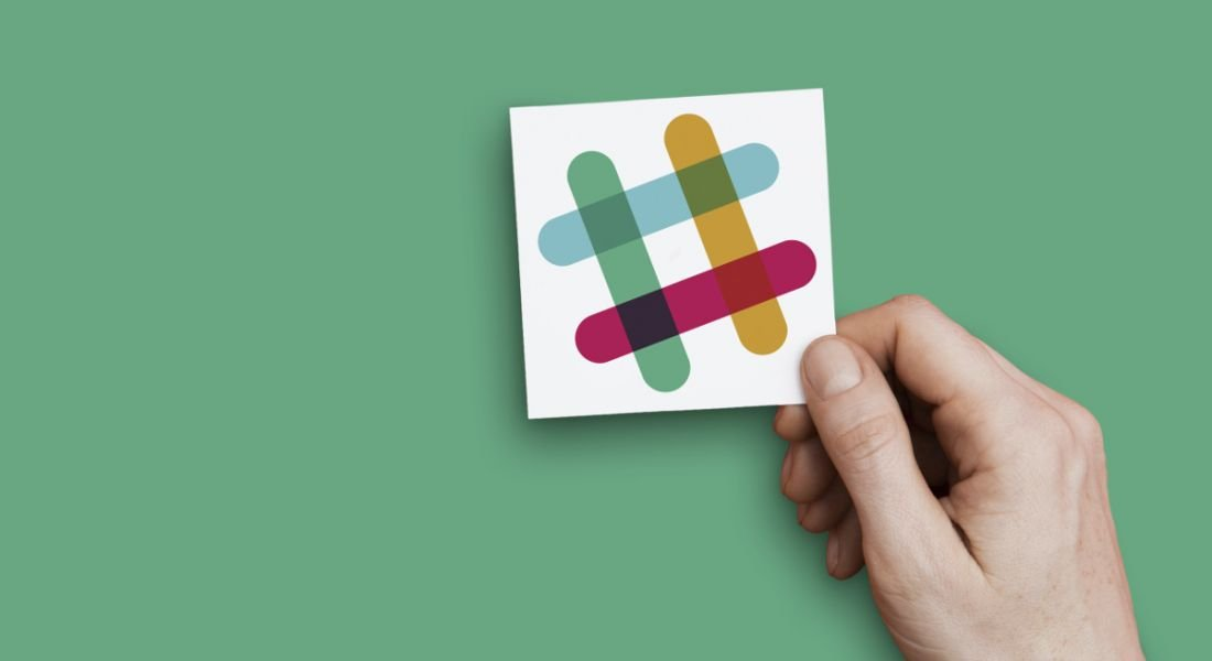 Hand holding the Slack logo against a green background.