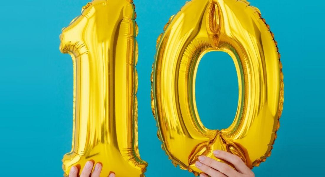 Gold foil number 10 celebration balloon on a blue background.