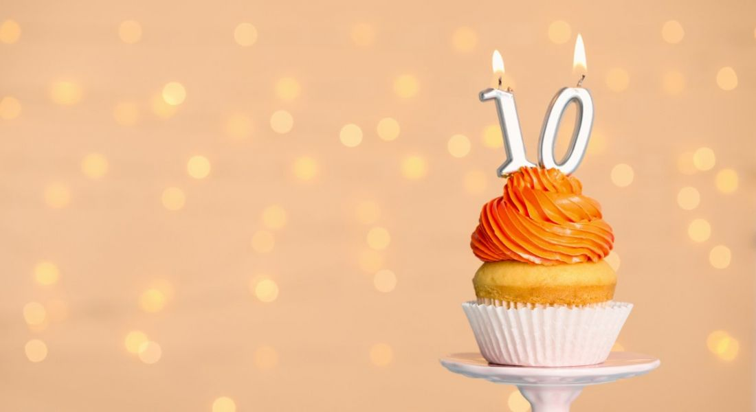 Orange-frosted birthday cupcake placed on a stand, with a number 10 candle on top of it.