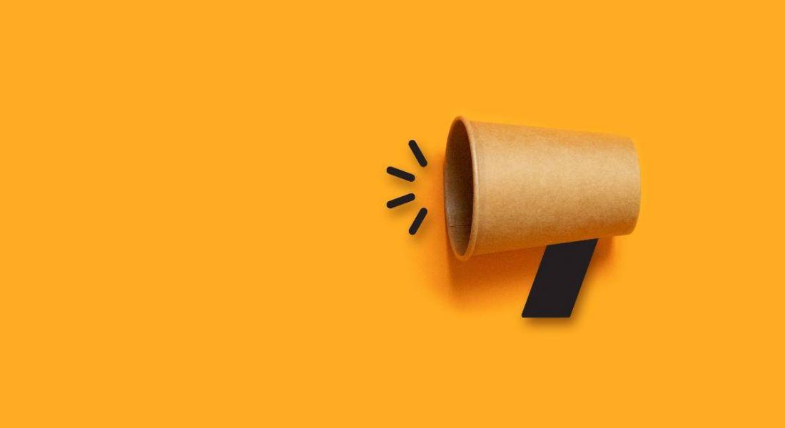 A cardboard megaphone against a dark yellow background.