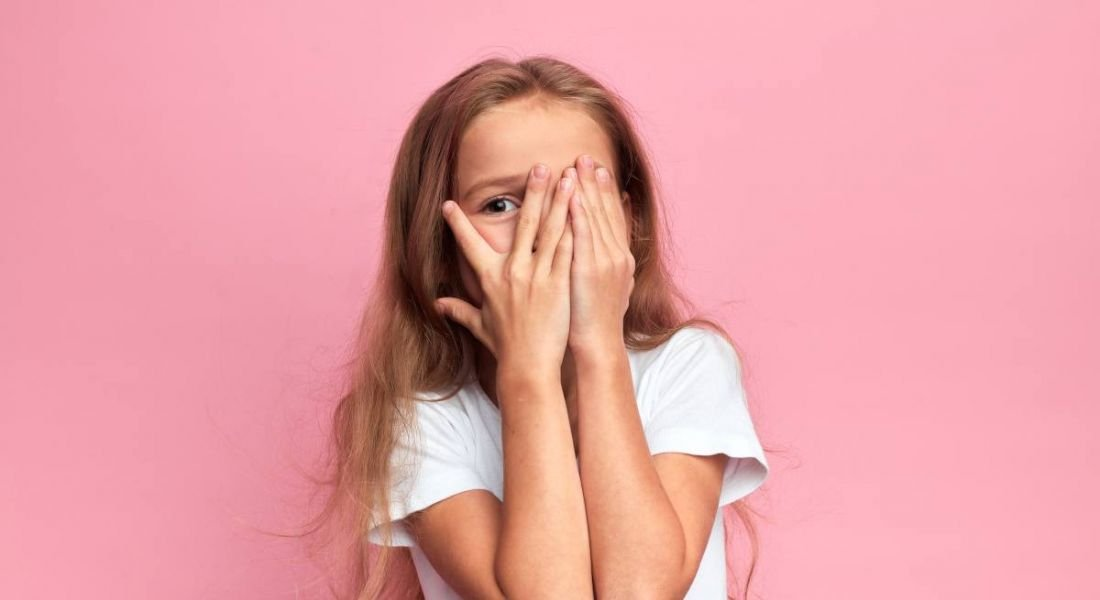 Little girl covering her face with her hands against pink background.