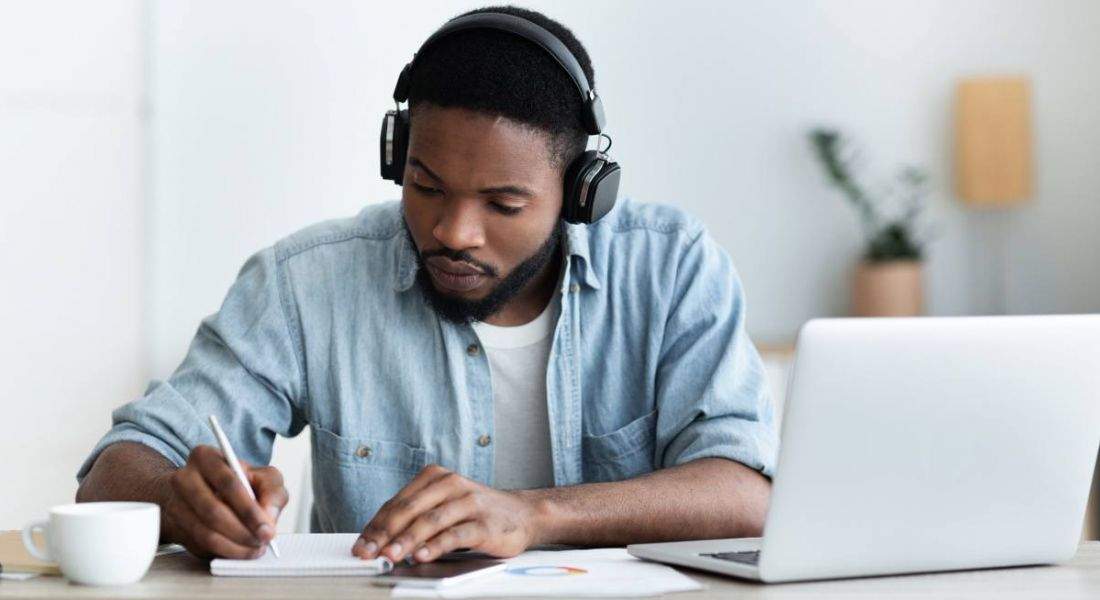 A man in casual clothes works at a desk with a pair of headphones on and a laptop in front of him.