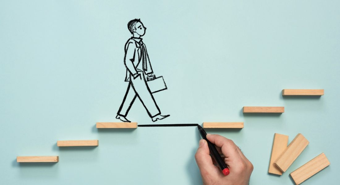 Business person drawn on a blue background with a hand drawing a step to fill a gap in the stairs he is walking up.