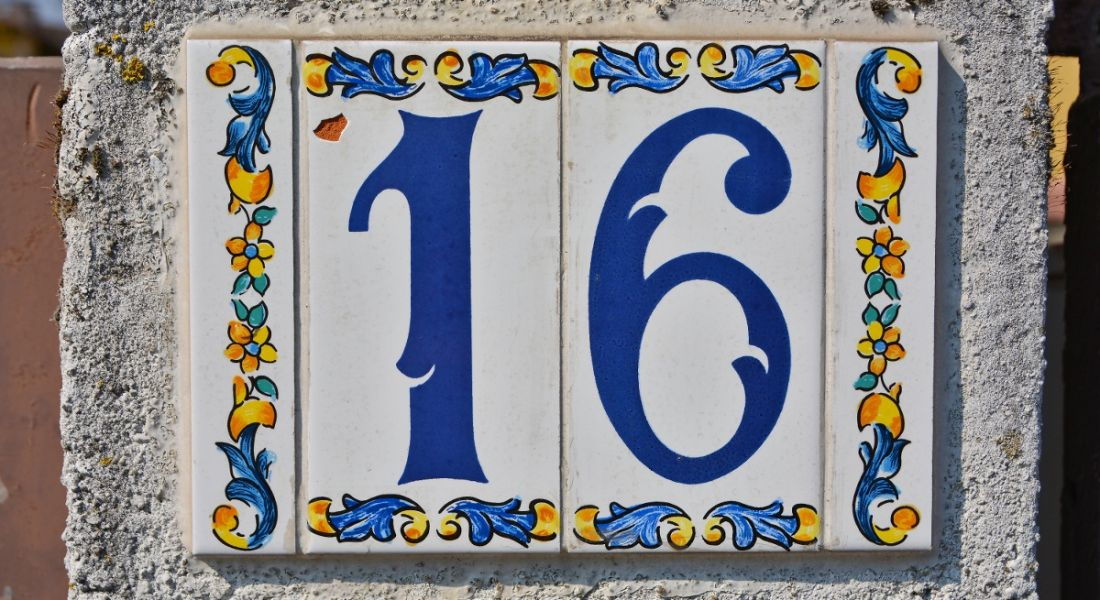 Number 16 printed on tiles on a white wall.