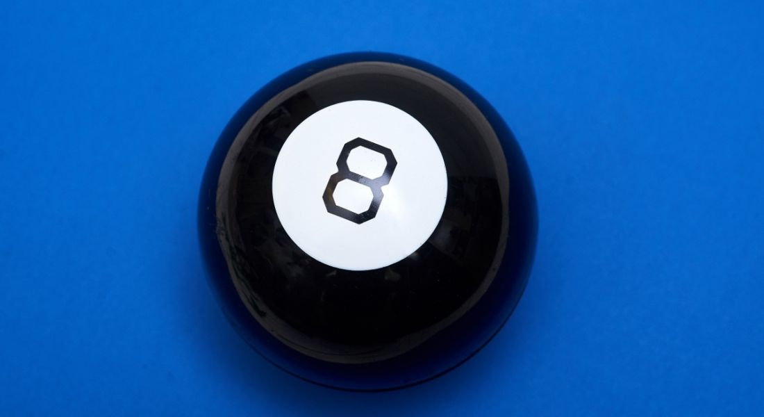A magic 8 ball, a large black plastic sphere with the number eight, on a strong blue background.