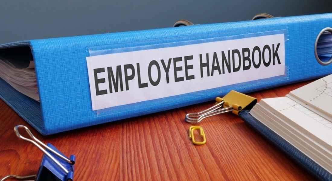 A blue employee handbook to onboard new staff on a wooden office desk.