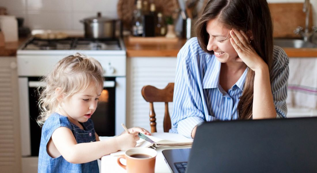 A woman is working from home using her kitchen as a remote office and is interacting with her young daughter.