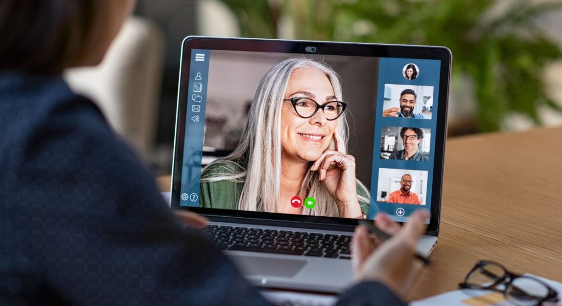 A manager is talking to one of their remote teams via a video call on a laptop.