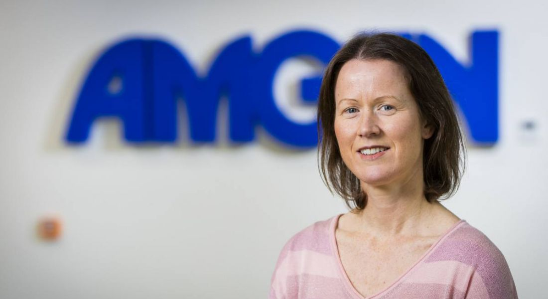 Eilis Murphy of Amgen is smiling into the camera, wearing a pink top and standing in front of a wall with a blue Amgen sign on it.