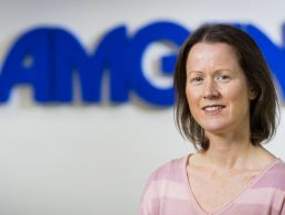 Michelle Somers is smiling into the camera in front of a wall with an Amgen sign.
