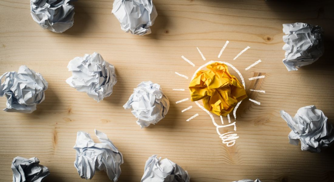 Scrunched up pieces of paper on a wooden table with one yellow and decorated like a light bulb.
