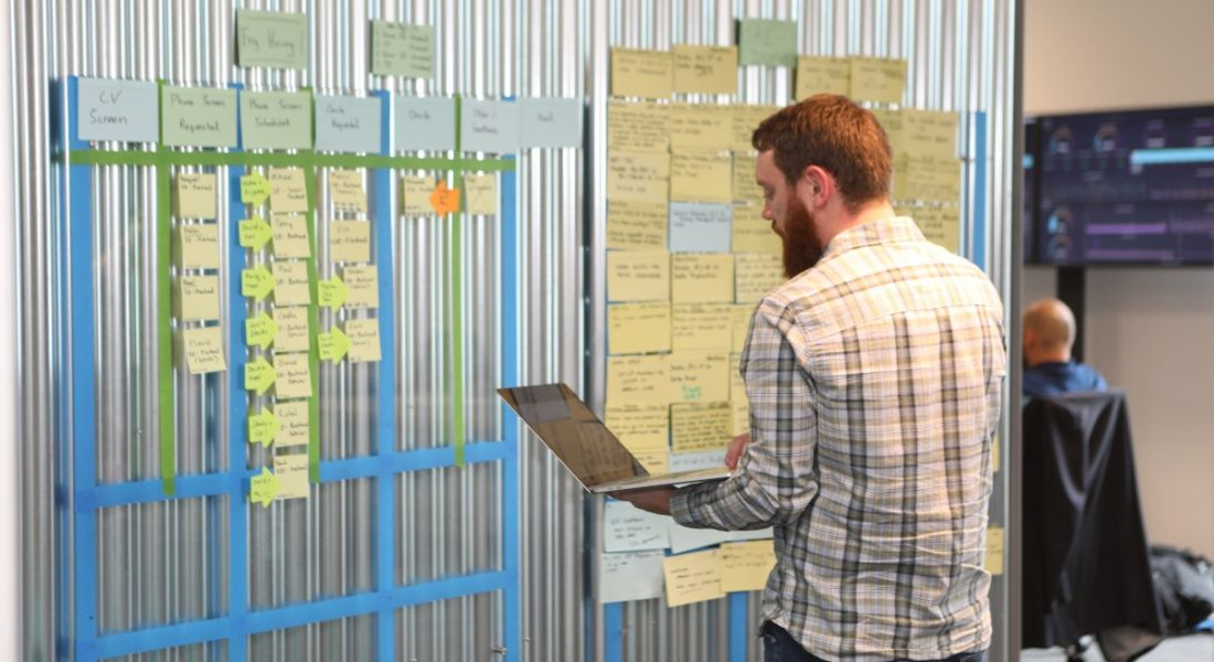 An employee at Viasat Ireland is standing with his laptop in front of a wall covered in post-it notes.