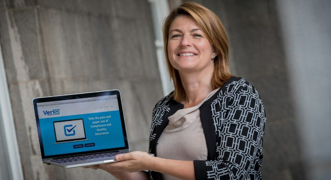 Ann Marie McSorley of Veri is holding up a laptop and smiling into the camera.