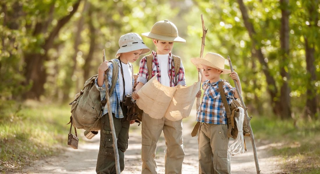 Three young boys are reading a map in adventurer clothes.
