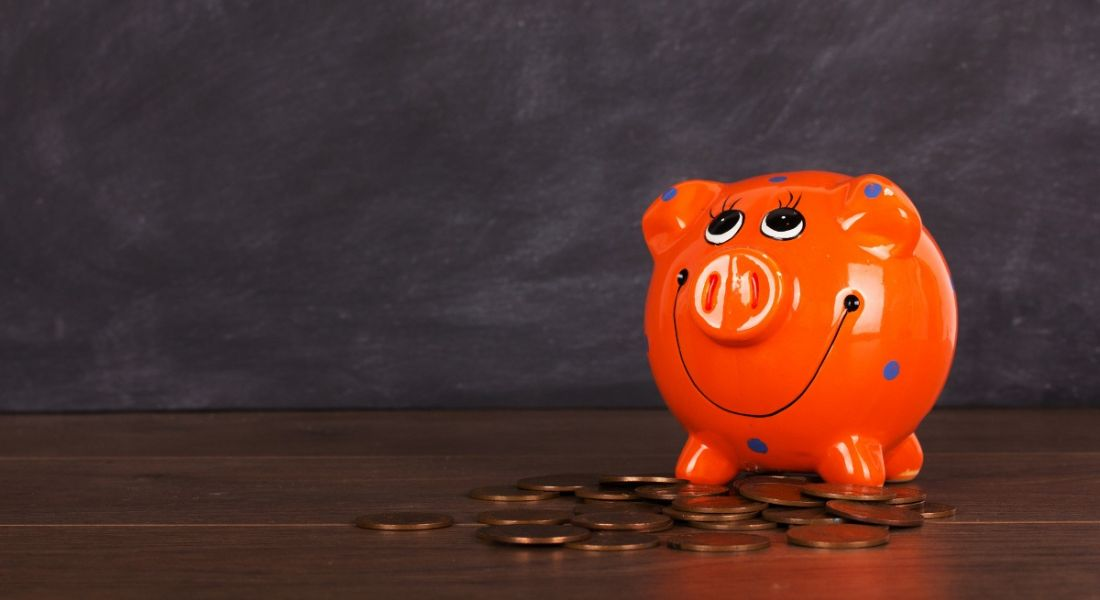 Coins and orange piggy bank on a wooden surface.