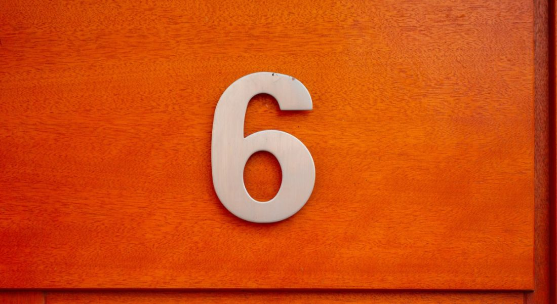 Number six door sign on red background.