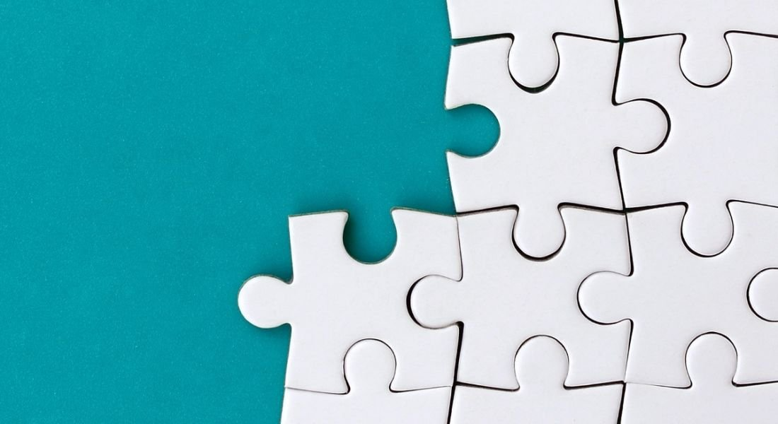White jigsaw puzzle pieces against a blue background.