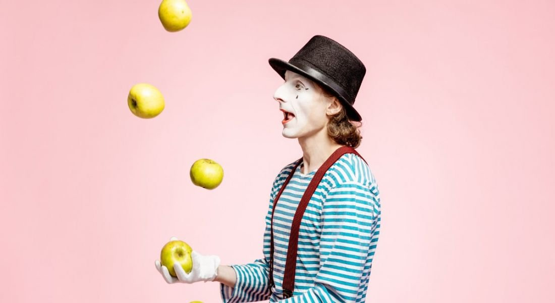Clown with white facial makeup juggling with apples against a pink background.