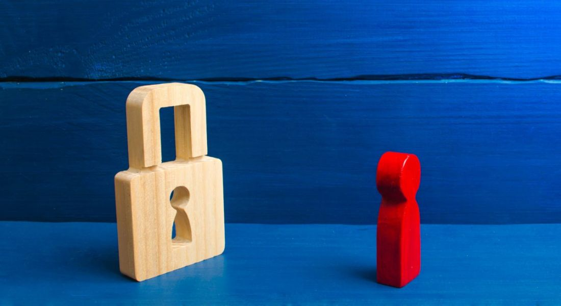 A red wooden figurine faces a wooden padlock against a dark blue background, symbolising the need for cybersecurity training.