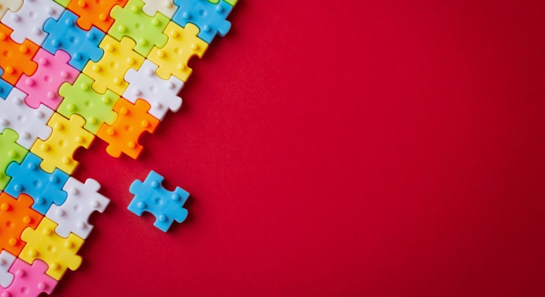 Colourful plastic jigsaw puzzle on red background.