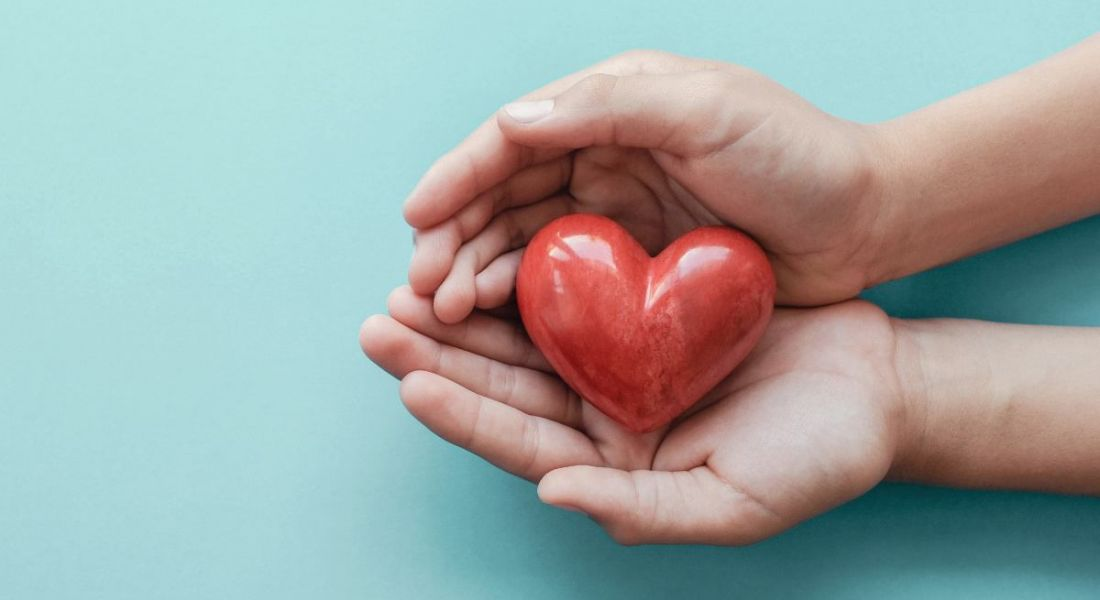 Hands holding red heart on blue background, symbolising health and wellbeing.