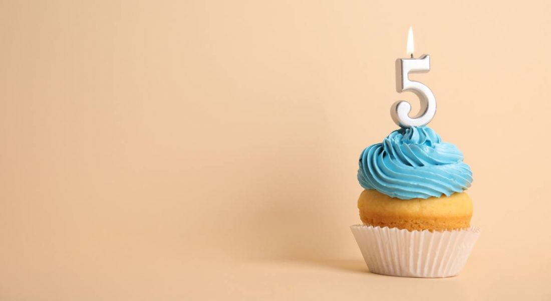 Birthday cupcake with number five candle on beige background.