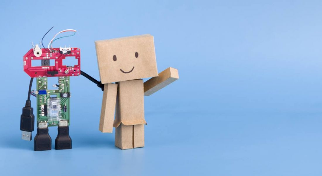 A small robot made of colourful parts is standing beside a small cardboard robot with a smiling face against a blue background.