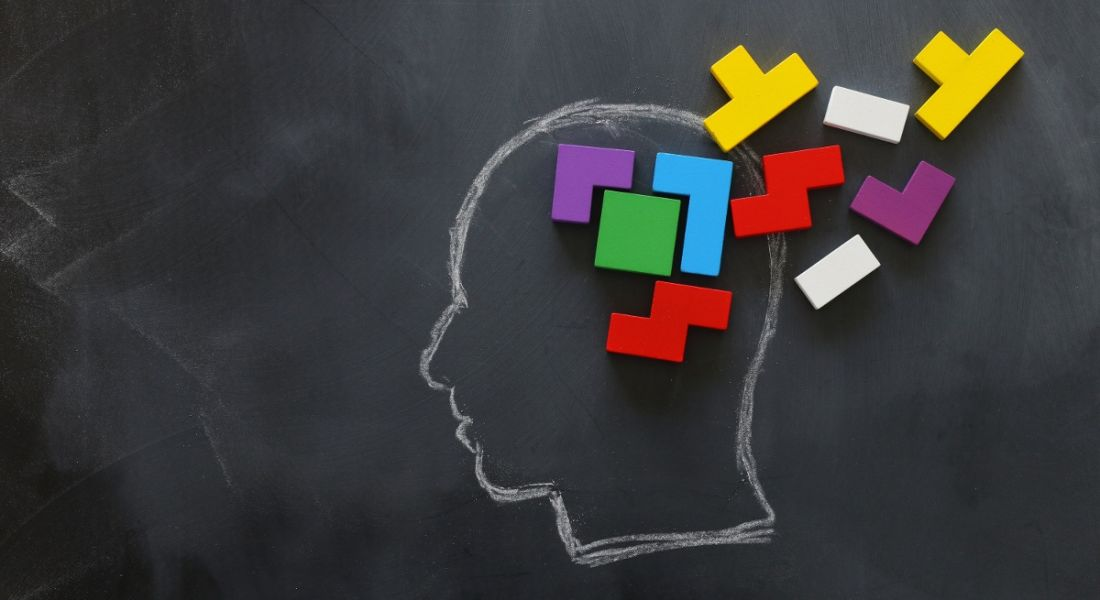 Brain made from colourful wooden puzzle inside chalk drawing of a human head on a blackboard.