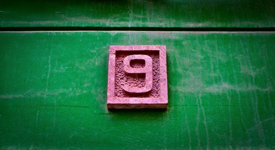 A pink number nine on a vivid green wall.