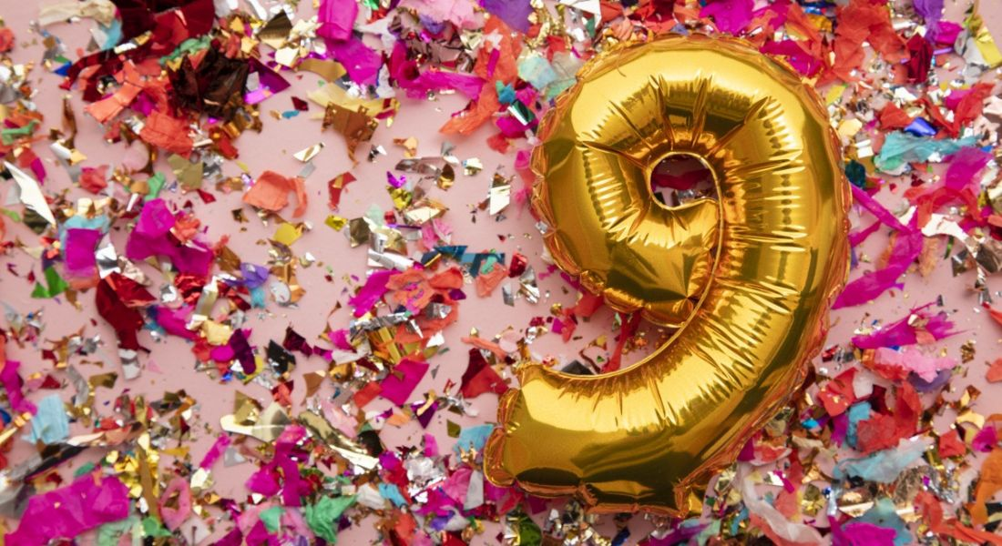 A foil number 9 balloon against a pink background and colourful confetti.