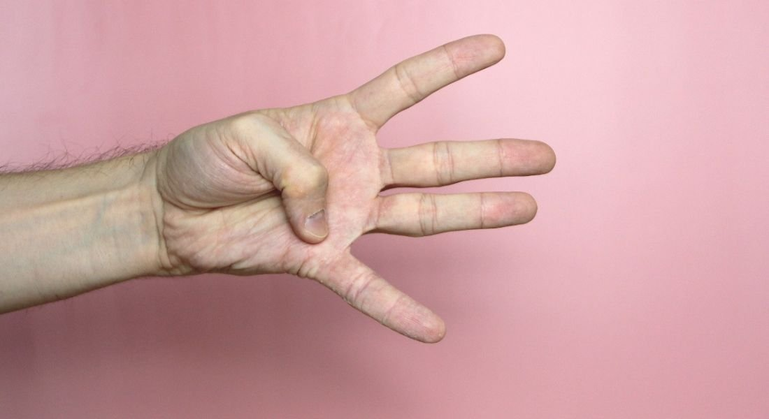 A hand is holding up four fingers against a pale pink background.