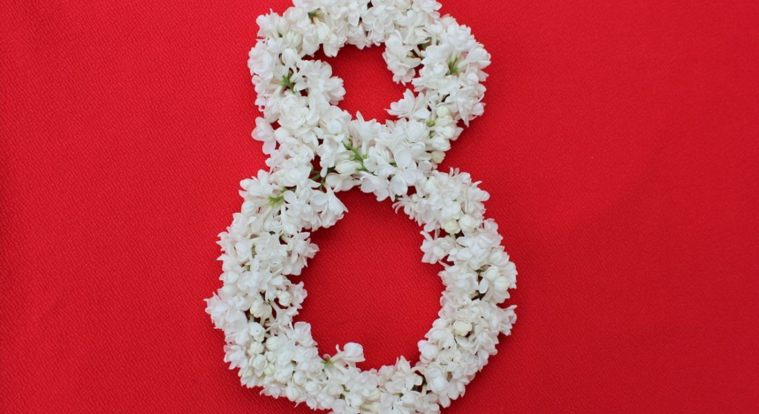 The number 8 is arranged in flowers against a red background.