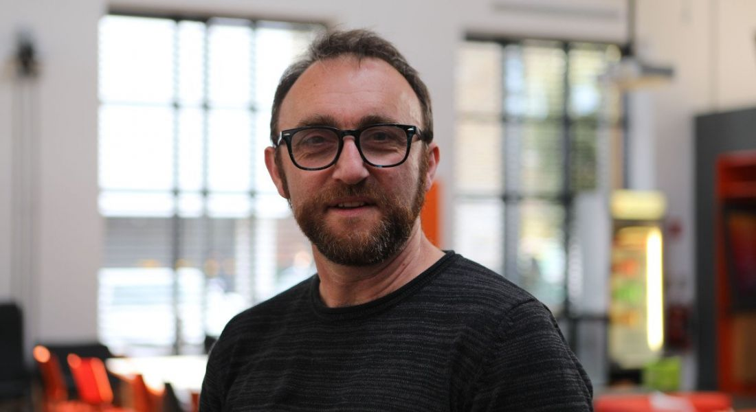 Owen Murray of Zalando Dublin is standing in a brightly lit office and smiling into the camera.