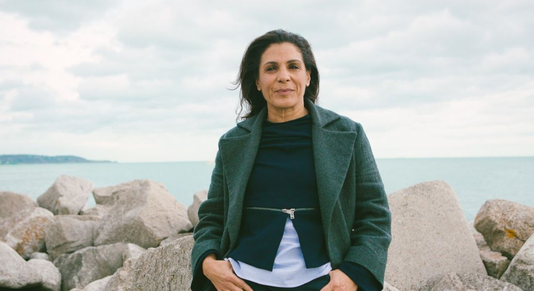 A woman with dark hair stands in front of a group of rocks in front of the ocean. She's wearing a green coat.
