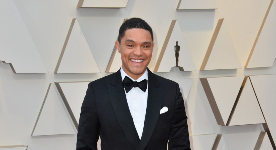 Trevor Noah stands smiling in a tuxedo against a white backdrop with geometric patterns.