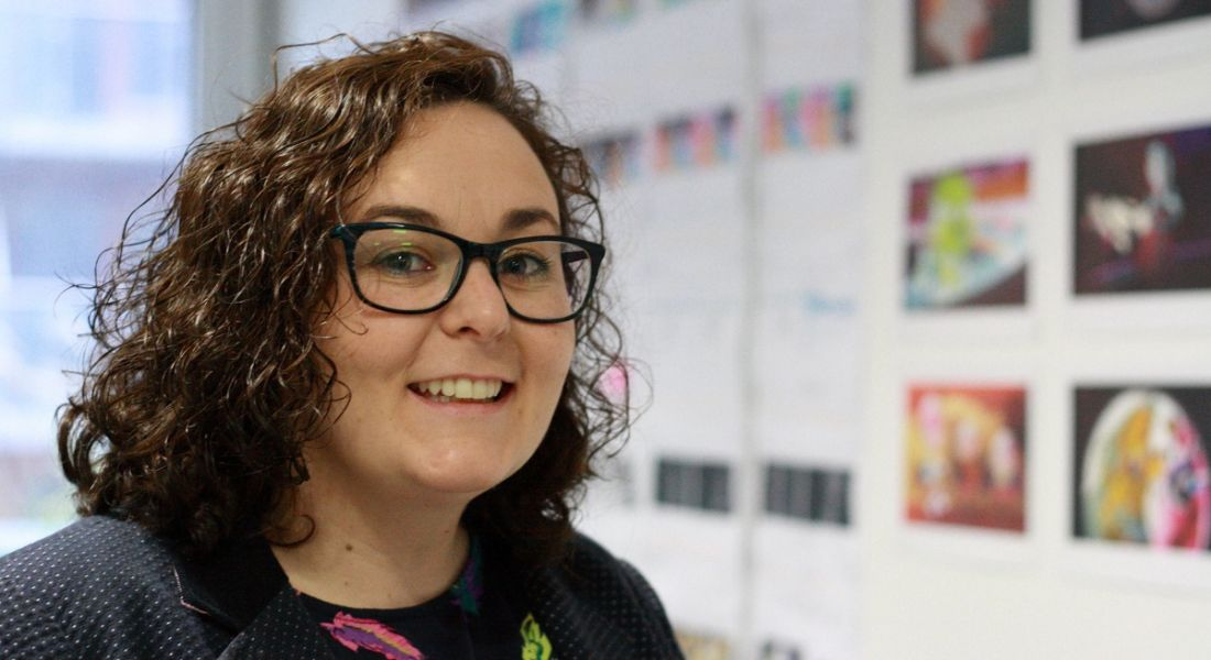 Niamh Herrity is smiling into the camera in front of a wall showcasing animations.