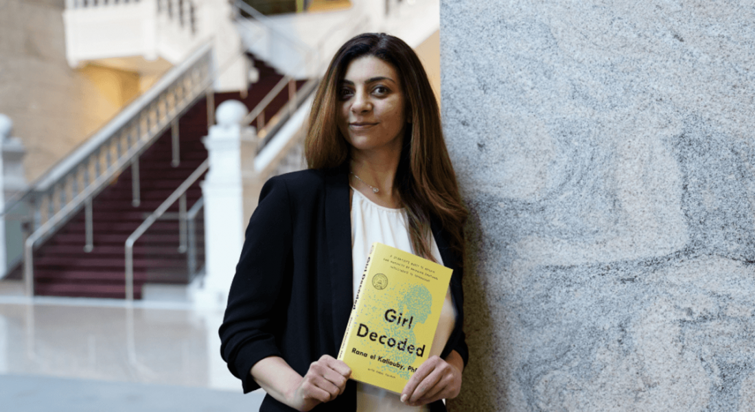 Rana el Kaliouby of Affectiva is standing in a brightly lit space and holding a copy of her book, Girl Decoded.