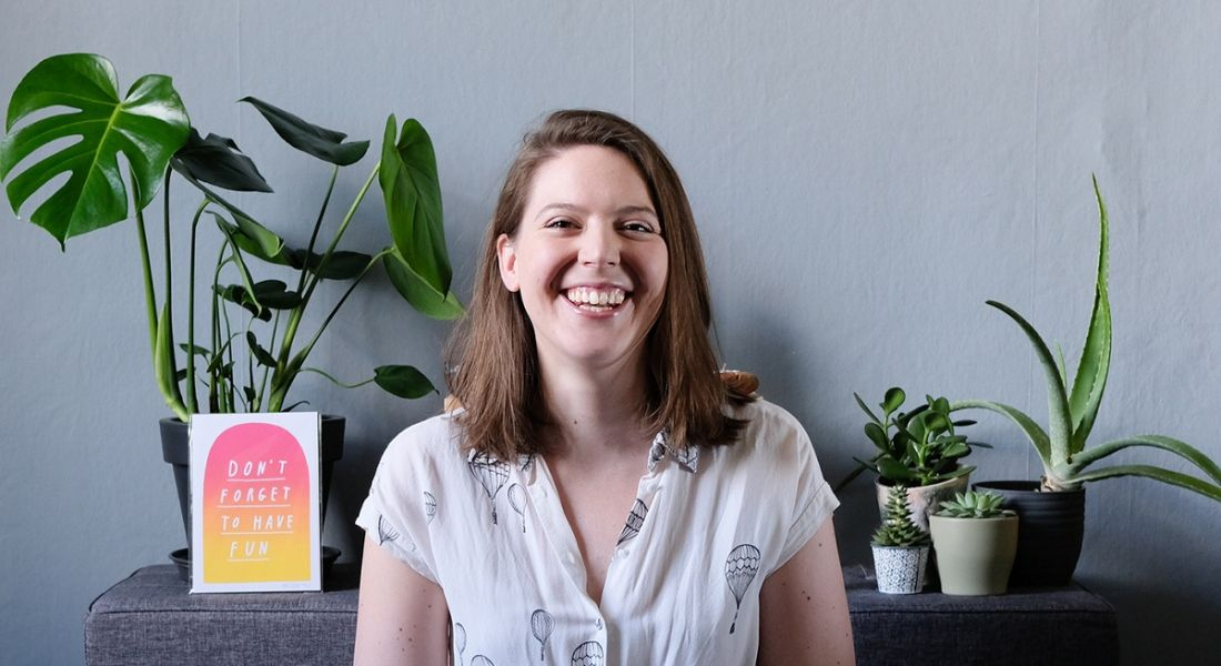 Lauren Pritchard of Viasat Ireland is smiling into the camera against a grey wall with plants.