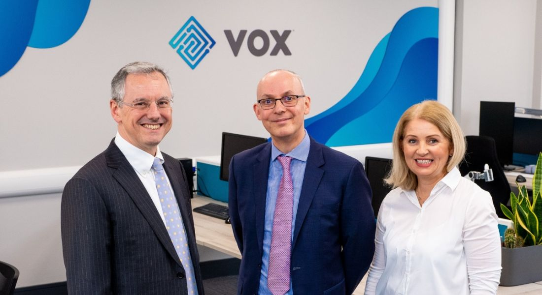 Three business people are standing together and smiling into the camera at the Vox Financial offices.