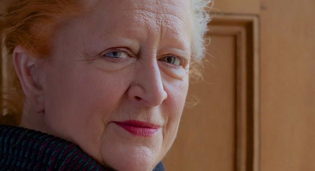 Margaret Heffernan is standing beside a brown wall and looking sideways into the camera.