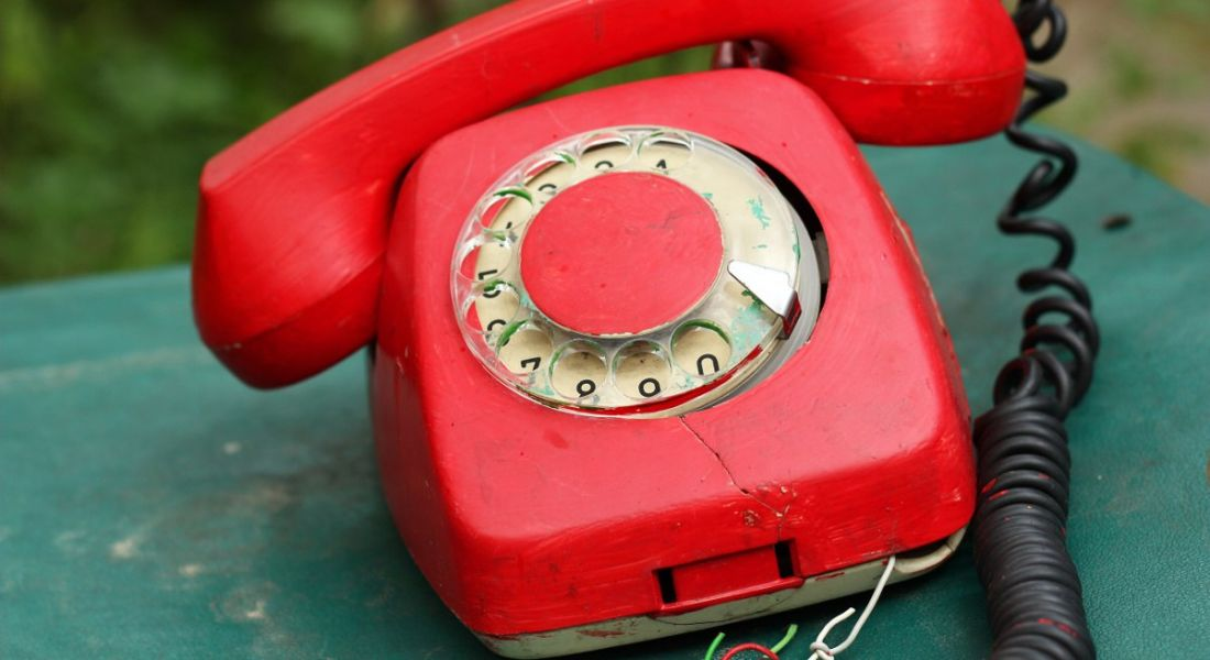 A broken red rotary telephone on a rusty green surface.