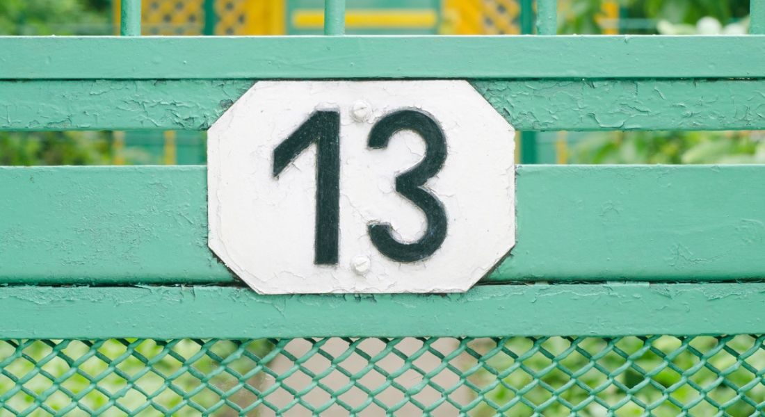 Number 13 sign on a teal metal fence.