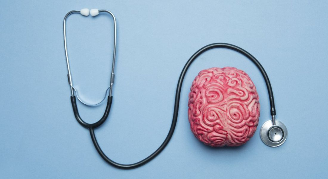 Human brain on a blue background with a stethoscope, symbolising mental health.