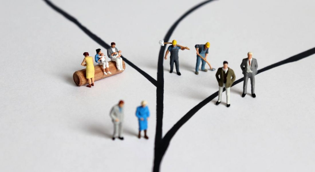 Miniature figures on a branched tree symbolising different roles in an economy, from businesspeople and construction workers to childcare workers.