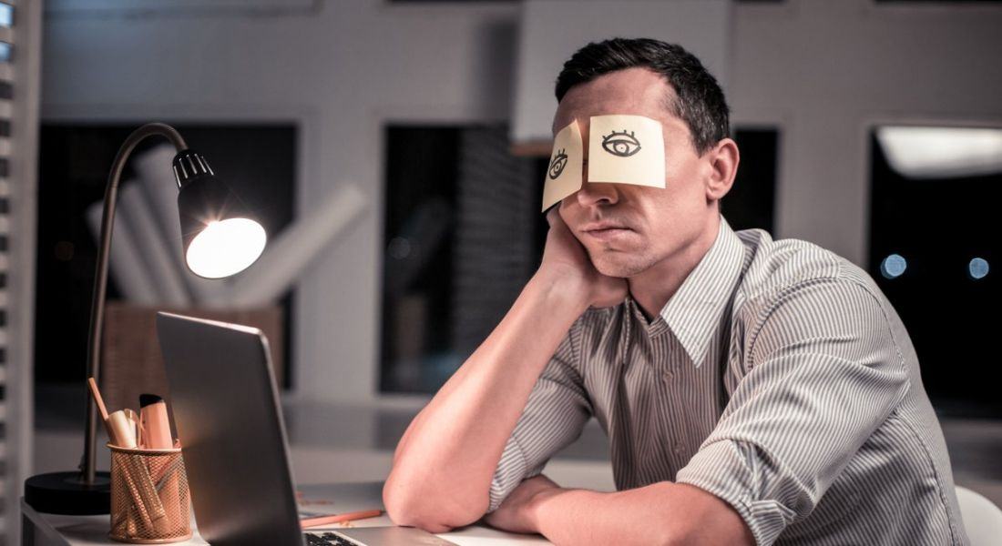 A man is sitting at his office desk with post-it notes stuck over his eyes. On the post-its are drawings of eyes to make it seem like he is awake.