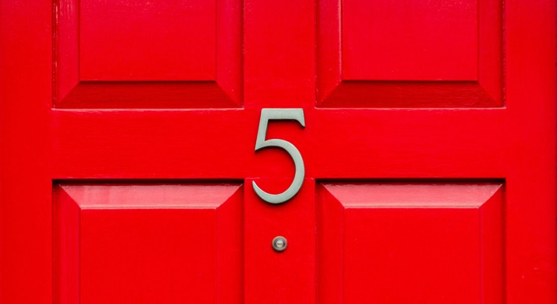 A gold number 5 on a bright red front door.
