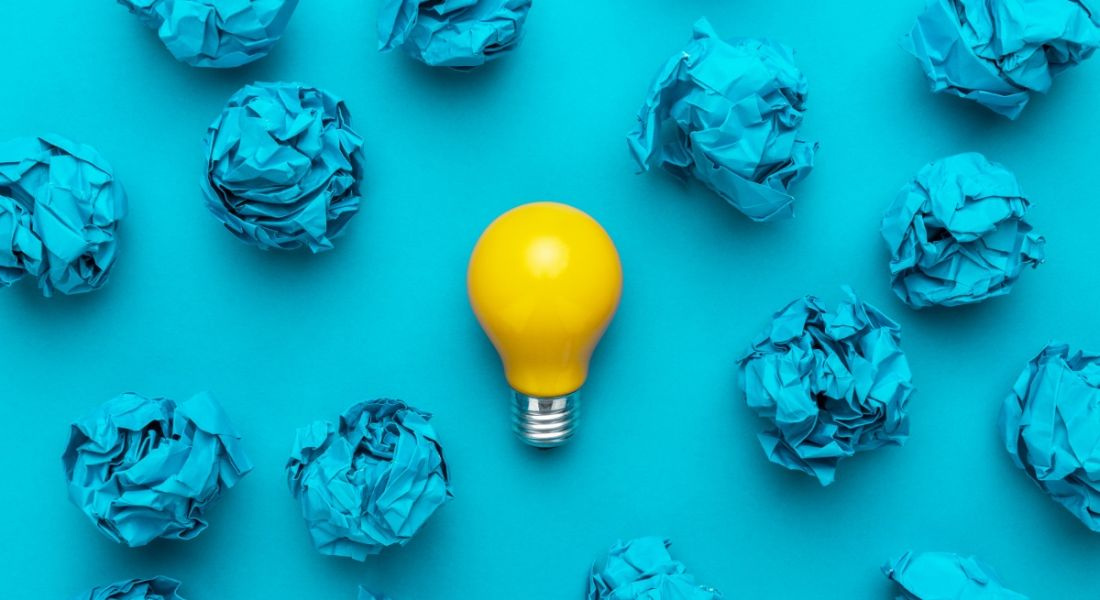 A yellow lightbulb surrounded by crumpled up blue pieces of paper against a blue background.